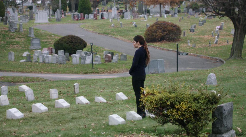 Shaw frente a la tumba de Root