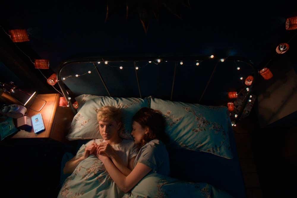 pareja lésbica de Feel Good en la cama